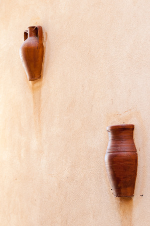 two terracotta vases set in a wall along the streets of Castelmola, Sicily photo