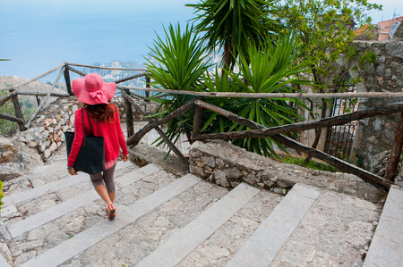 taormina: Girl walking down the stairs leading to the castle of Castelmola, a small tourist village near Taormina, Sicily