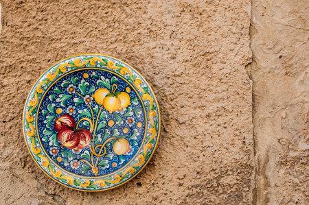 View of a colored ceramic plate from Caltagirone hung on the wall of a street Фото со стока