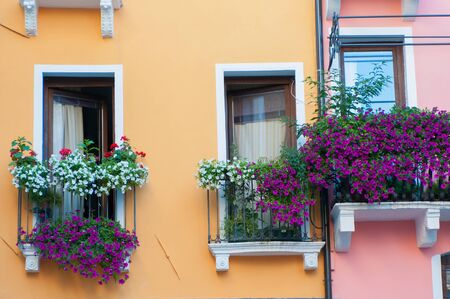 View of a flowered balcony of a wooden window in a house of the town center of Vicenza photo