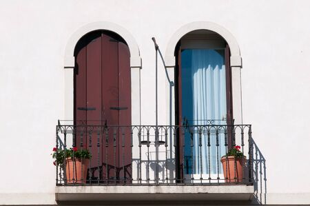 View of balcony with two typical wooden arch window in a house of the town center of Vicenza photo