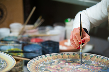 decorator: Pottery decorator from Caltagirone while finishing a ceramic dish in her work space Stock Photo