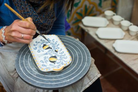 Pottery decorator from Caltagirone while finishing a ceramic dish in her work space Фото со стока