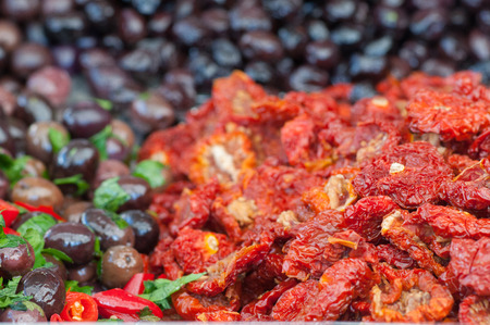 Dry peppers in oil and seasoned black olives in a sicilian weekly market Stock Photo