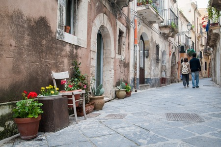 syracuse: View of one typical street in Ortigia, the old part of Syracuse, and some ornamental flowered vases in the foreground and a couple walking Stock Photo