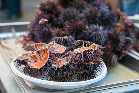 Cut sea urchins laid on a dish for sale in the public fishmarket of Catania, Sicily