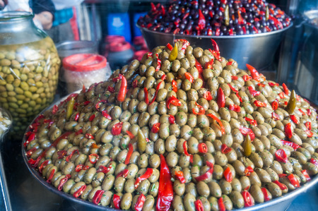 pimiento: Piramidal heap of green olives and red pepper in a Sicilian public market