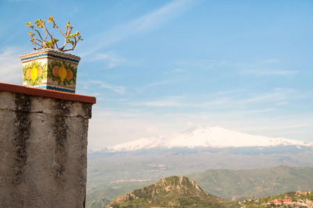 Snowy Mount Etna seen from a panoramic terrace of the small town Castelmola, near Taormina, with a painted ceramic vase on the left photo