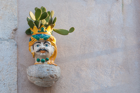 Characteristic ceramic head shaped planter with a prickly pear, set into the stone wall of a house along the streets of Castelmola, Sicily Stok Fotoğraf - 39953456
