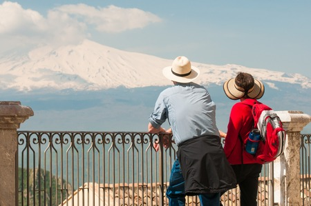 Two tourists admiring Mount Etna from a panoramic balcony of Castelmola, Sicily Stock Photo