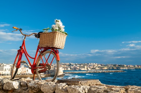 Old red bicycle in September in a wall along the seafront of Syracuse Sicily and the town in the distance Stok Fotoğraf - 40211569