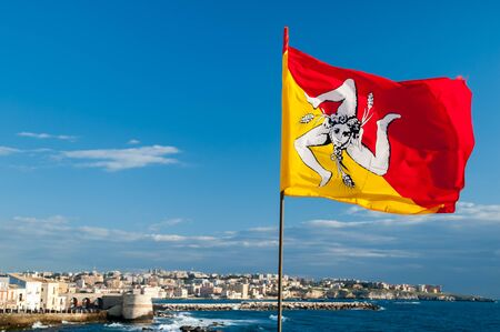 region sicilian: The waving flag of Scily along the seafront of Syracuse with a view of the town