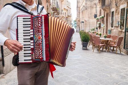ortigia: Accordion musician playing along the alleys of the old part of Syracuse Ortigia Stock Photo