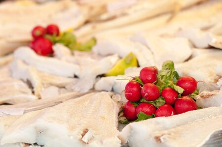 stockfish: Radishes and parsley laid on stockfish in a fishmarket
