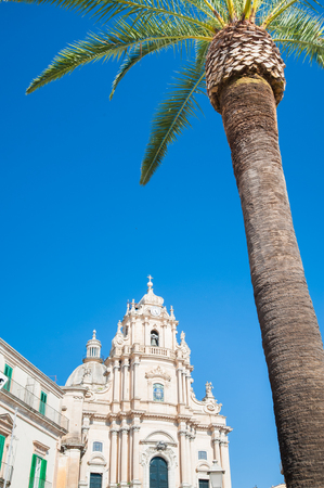 ragusa: Palm tree in the main square of Ragusa Ibla, Sicily, with the baroque church of St. George Stock Photo