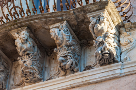 historical periods: View of some typical baroque mascarons under the balconies of Cosentini Palace in Ragusa Ibla, Sicily