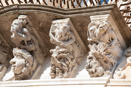 ragusa: View of some typical baroque mascarons under the balconies of Cosentini Palace in Ragusa Ibla, Sicily