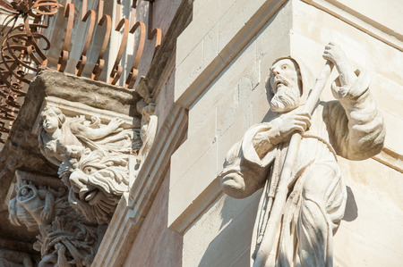ragusa: The baroque statue of St. Francis of Paola sculpted at the corner of Cosentini palace in Ragusa Ibla with some mascarons under its balconies