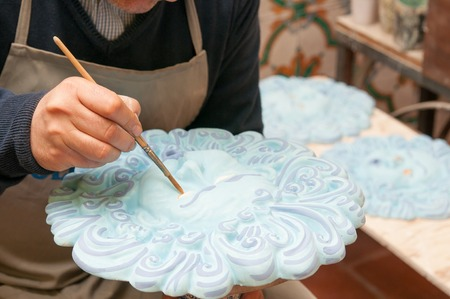designates: Artist decorating a typical blue ceramic sun in its studio in Caltagirone Stock Photo