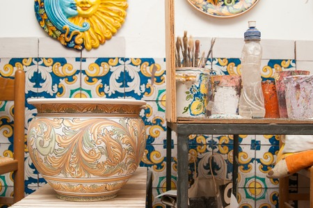 designates: Decorated ceramic vase in the workshop of a decorator of Caltagirone and a worktable with tools Stock Photo