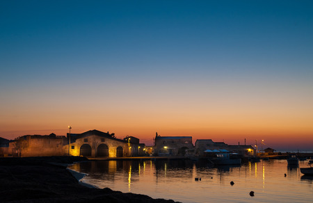 Dawn in the small harbor of the fishing village Marzamemi, Sicily, and the enlightened tonnara