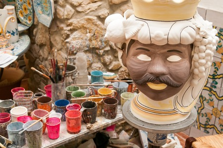 designates: Ceramic head of an arab man in the study of a decorating artisan in Caltagirone and glasses for colors in the background