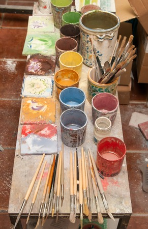 decorator: Work table of a decorator pottery of Caltagirone with different colored containers and paintbrushes