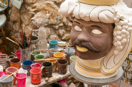 designates: Ceramic head of an arab man in the studio of a decorating artisan in Caltagirone and glasses for colors in the background Stock Photo