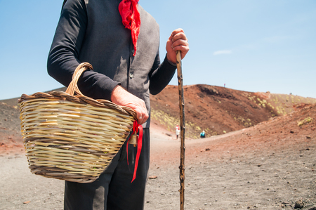 characteristic: View of a folkloristic Sicilian shepherd with his characteristic red scarf and a wicker basket close to one of Mount Etna side craters Stock Photo