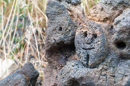 rudimentary: Lava stone sculpture of a stylised mans face