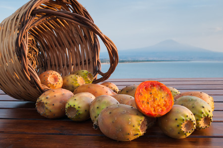 Wicker basket full of prickly pears on a wooden table with sea and Mount etna in the background Stock Photo