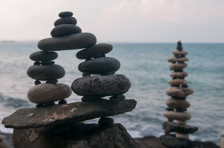 Stone piles made along a beach and the sea in the background Stock Photo