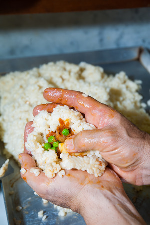 filling in: Sicilian cook filling in small heaps of rice to make the typical regional arancini