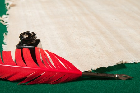 inkwell: Red quill pen and black inkwell on a papyrus sheet