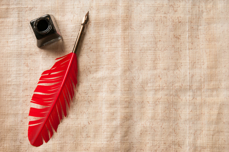 Quill pen on a papyrus sheet Stock Photo