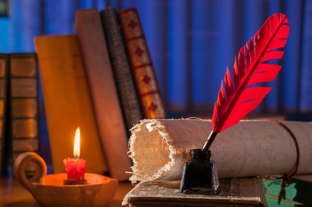 ancient papyrus: Red quill pen, black inkwell and a rolled papyrus sheet enlightened by a candle on a blue background Stock Photo