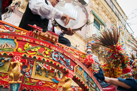 folkloristic: Close up view of a colorful wheel of a typical sicilian cart and a folkloristic tambourine player on it