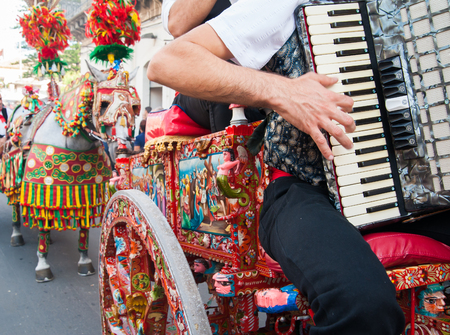 characteristic: Accordion player wearing a folkloristic dress and playing on a characteristic sicilian cart