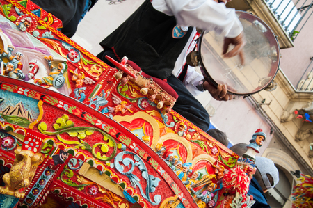 folkloristic: Close up view of a colorful wheel of a typical sicilian cart and to folkloristic tambourine player on it