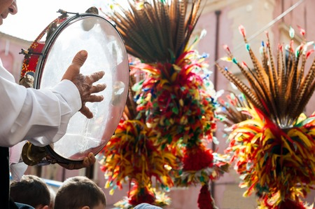 folk heritage: Close up view of a colorful wheel of a typical sicilian cart and to folkloristic tambourine player on it