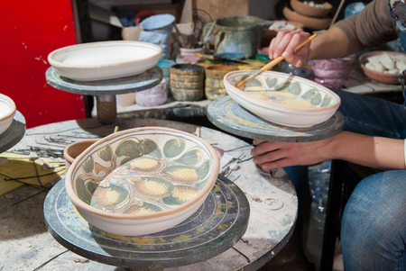 Decorated ceramic tray in the work table of a pottery artisan at work, Caltagirone 版權商用圖片