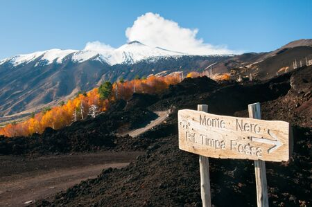 volcano slope: Wooden sign on the lava stone of the nothern side of Mount Etna and a view of the snowy peak Stock Photo