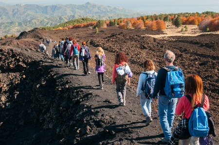 Group of young hikers walking on a trail leading to the north side of Mount Etna Stok Fotoğraf - 48568875