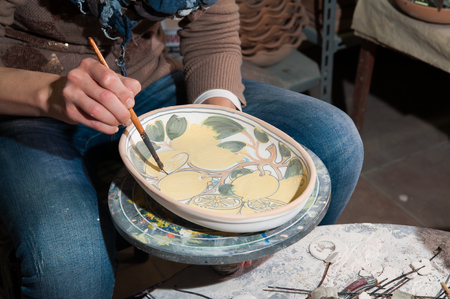 decorator: Pottery decorator from Caltagirone while finishing a ceramic tray in her work space
