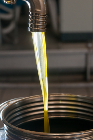 oil mill: Finished olive oil running from a steel tap into a metal tank in an oil mill Stock Photo