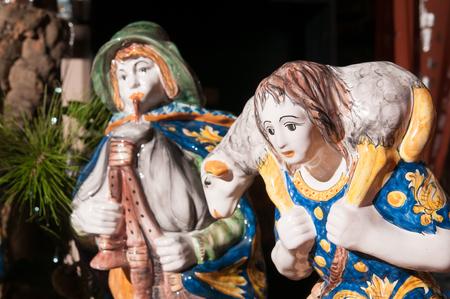 pastor de ovejas: Estatua de cerámica pintada interpretando a un pastor y su pequeña oveja de un belén de cerámica por un artesano en Caltagirone Foto de archivo