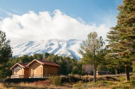 humo: Northern side of snowy Mount Etna with some pine trees and two refuges