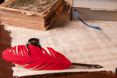 an feather: Red quill pen and black inkwell on a papyrus sheet