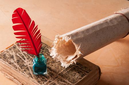medievales: pluma de ave roja y una hoja de papiro enrollado en un viejo libro Foto de archivo