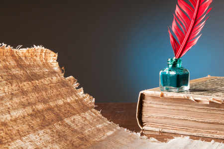 papyrus: Red quill pen and a papyrus sheet on a wooden table in a blue background Stock Photo